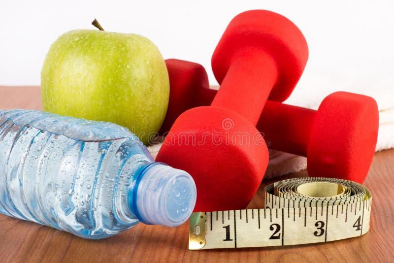 Fin d'haltère rouge, d'eau dans la bouteille, de pomme fraîche verte avec la rosée et de bande de mesure sur le plancher en bois photos libres de droits