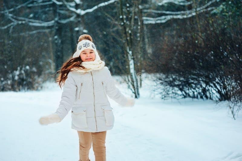 Fin d'hiver vers le haut de portrait de fille rêveuse mignonne d'enfant dans le manteau, le chapeau et des mitaines blancs images libres de droits