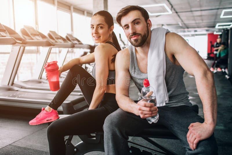 Fin d'un beau couple se reposant sur le banc et la pose de sport Également ils sont eau potable de leurs bouteilles image libre de droits