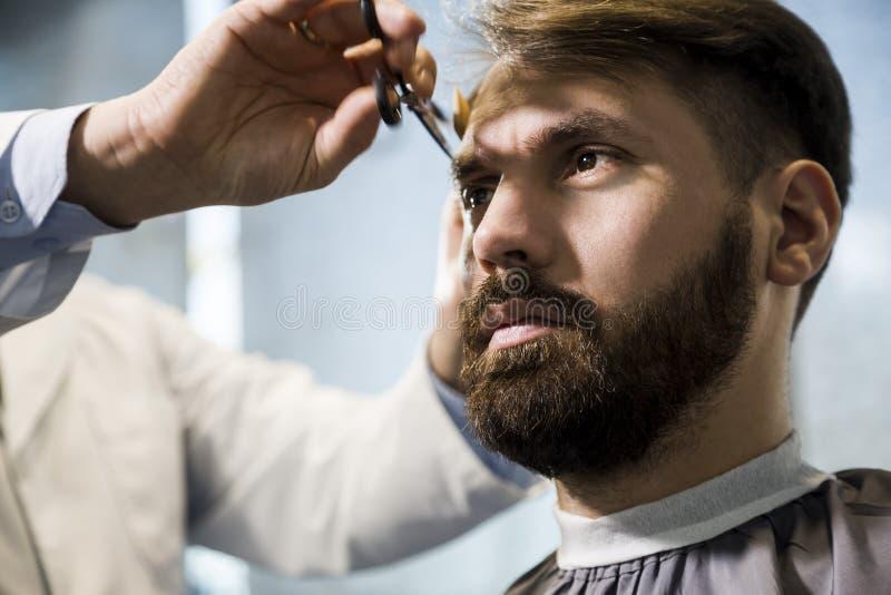 Fin d'un homme ayant sa coupe de cheveux images libres de droits