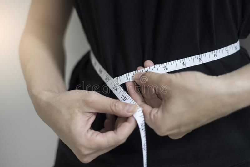Fin de concept de régime vers le haut des femmes mesurant la circonférence de taille photo stock