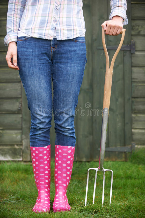 Fin de femme portant Wellingtons rose tenant la fourchette de jardin photographie stock libre de droits