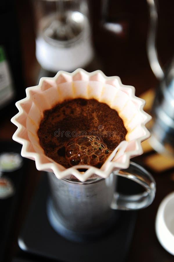 Fin de floraison de café dans le dispositif d'écoulement en céramique rose d'origami avec le filtre de papier Brassage manuel alt photos libres de droits