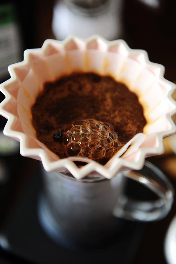 Fin de floraison de café dans le dispositif d'écoulement en céramique rose d'origami avec le filtre de papier Brassage manuel alt image libre de droits