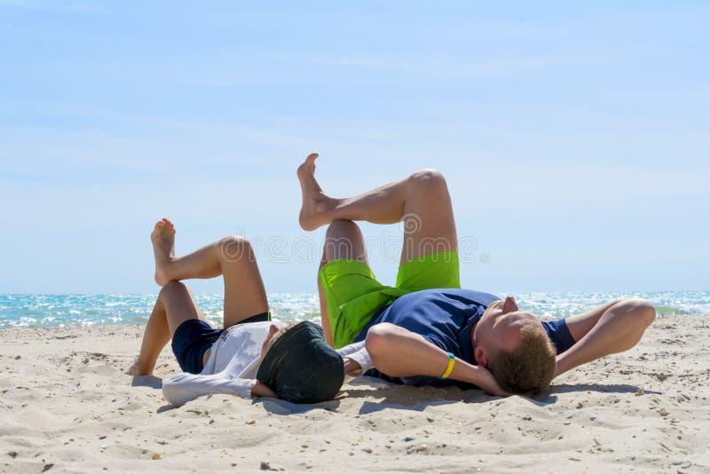Fin de semana en la playa El papá y el hijo miente en la playa Papá e hijo que se relajan en la playa imágenes de archivo libres de regalías
