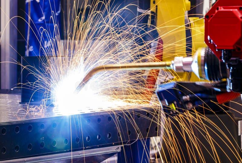 Fin de soudure de processus de robot vers le haut de la coupe de laser du métal sur le bras robotique avec des étincelles image libre de droits