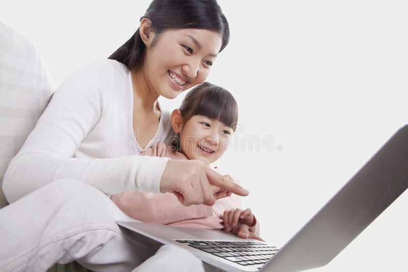 Fin de sourire et se reposante de mère et de fille ensemble sur le sofa, employant et se dirigeant à l'ordinateur portable, inclin photos libres de droits