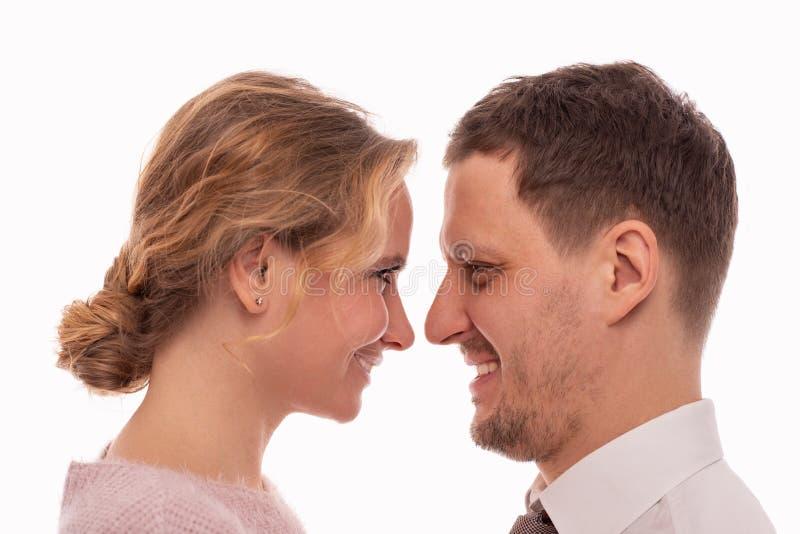Fin de studio vers le haut de portrait d'un peuple de sourire positif d'homme et de femme regardant l'un l'autre avec amour photographie stock