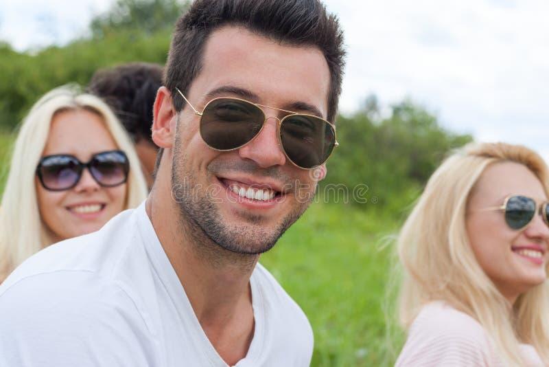 Fin de visage d'homme vers le haut d'herbe verte extérieure, sourire heureux de lunettes de soleil de personnes image libre de droits