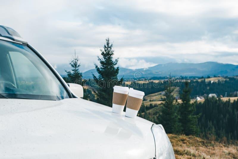Fin de voiture avec deux tasses de café sur les montagnes de capot sur le fond images stock