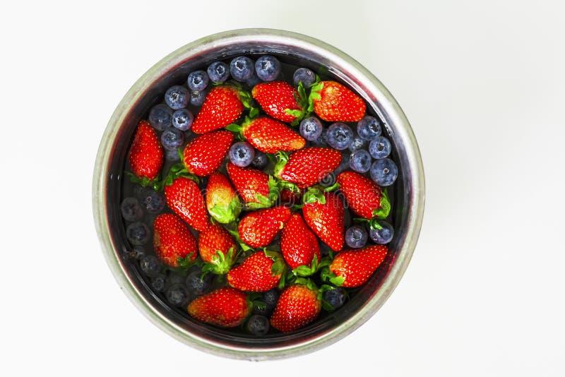 Fin de vue supérieure vers le haut des fraises et des myrtilles fraîches dans une cuvette d'acier inoxydable sur un fond blanc, c photographie stock