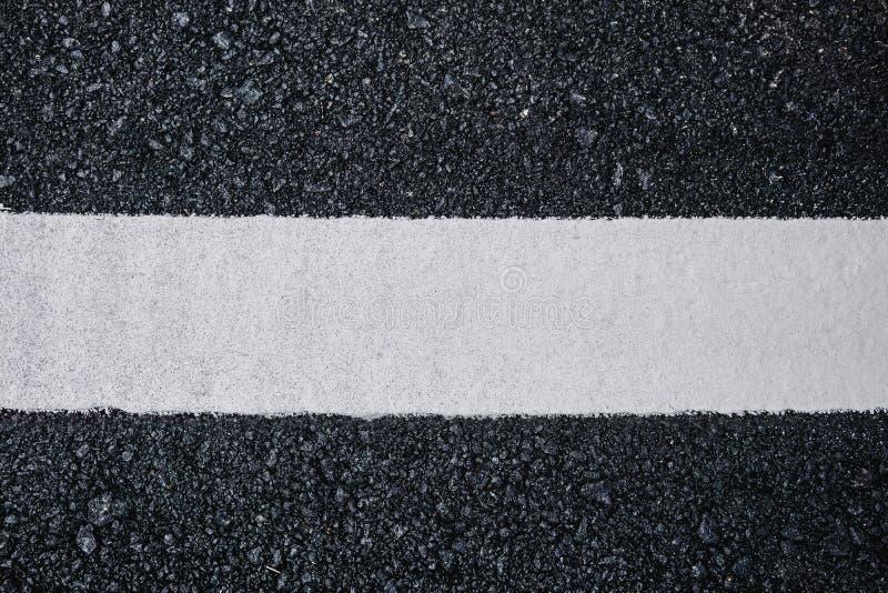 Fin de vue supérieure vers le haut de fond de texture de route goudronnée avec la ligne blanche images libres de droits