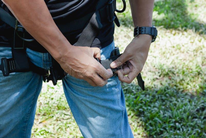 Fin douce de foyer vers le haut d'usage asiatique de jeune homme le harnais de sécurité image stock