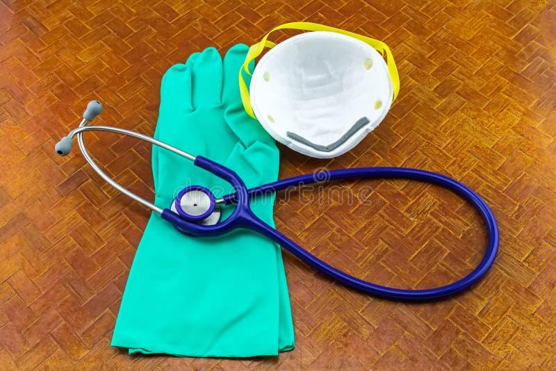Fin du masque blanc, du gant bleu et de la pile de stéthoscope sur le blac images libres de droits
