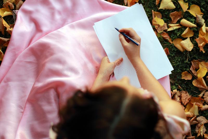 Fin emotionell brunetthandstil på papper, sammanträde på höstsidor och gräs kopiera avstånd fotografering för bildbyråer
