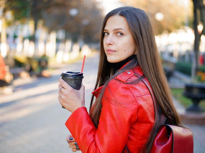 Fin extérieure vers le haut de tir de femme élégante de brune de l'année 20s dans le manteau en cuir rouge sur le café ou le thé  photo stock