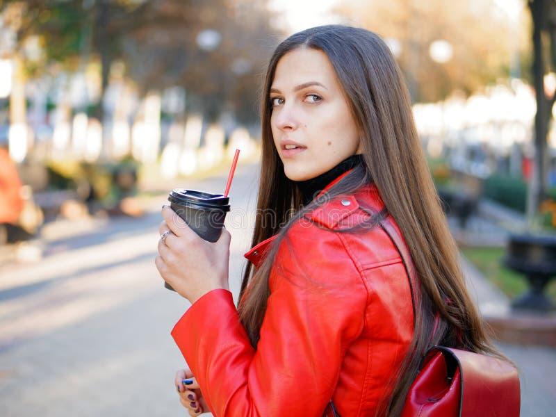 Fin extérieure vers le haut de tir de femme élégante de brune de l'année 20s dans le manteau en cuir rouge sur le café ou le thé  image libre de droits