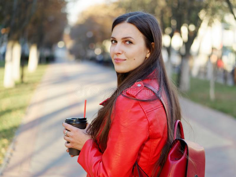 Fin extérieure vers le haut de tir de femme élégante de brune de l'année 20s dans le manteau en cuir rouge sur le café ou le thé  photographie stock libre de droits