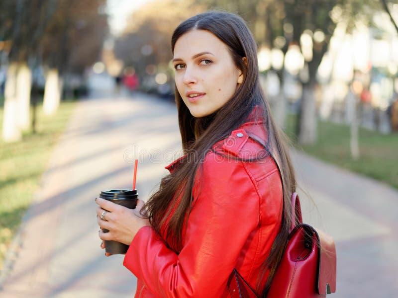 Fin extérieure vers le haut de tir de femme élégante de brune de l'année 20s dans le manteau en cuir rouge sur le café ou le thé  image stock