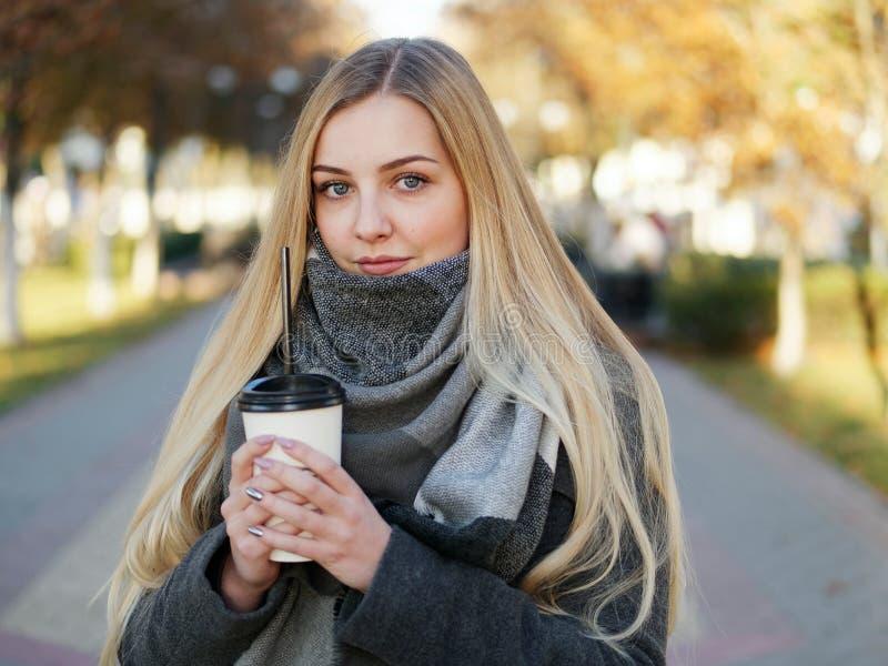 Fin extérieure vers le haut de tir de femme blonde élégante de l'année 20s dans l'écharpe sur le café ou le thé potable de pause  photos libres de droits