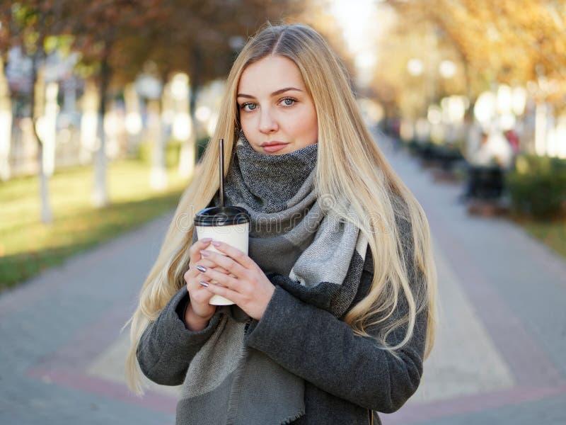 Fin extérieure vers le haut de tir de femme blonde élégante de l'année 20s dans l'écharpe sur le café ou le thé potable de pause  photos stock
