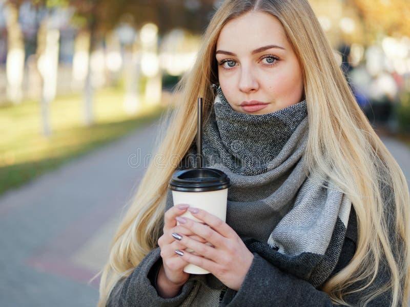 Fin extérieure vers le haut de tir de femme blonde élégante de l'année 20s dans l'écharpe sur le café ou le thé potable de pause  images stock