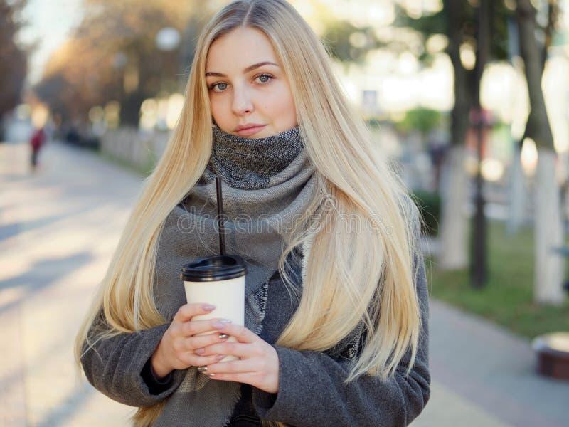 Fin extérieure vers le haut de tir de femme blonde élégante de l'année 20s dans l'écharpe sur le café ou le thé potable de pause  image libre de droits