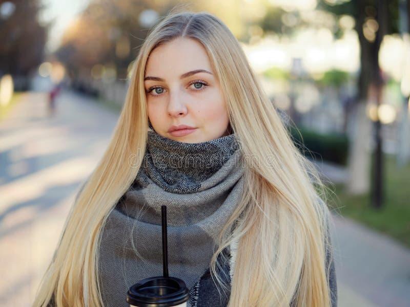 Fin extérieure vers le haut de tir de femme blonde élégante de l'année 20s dans l'écharpe sur le café ou le thé potable de pause  images libres de droits
