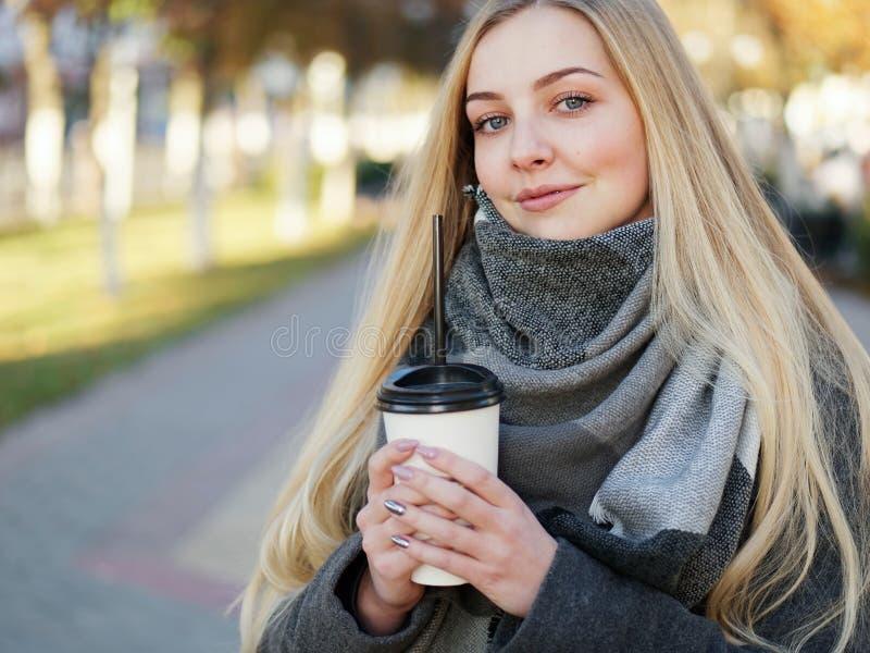 Fin extérieure vers le haut de tir de femme blonde élégante de l'année 20s dans l'écharpe sur le café ou le thé potable de pause  photo libre de droits