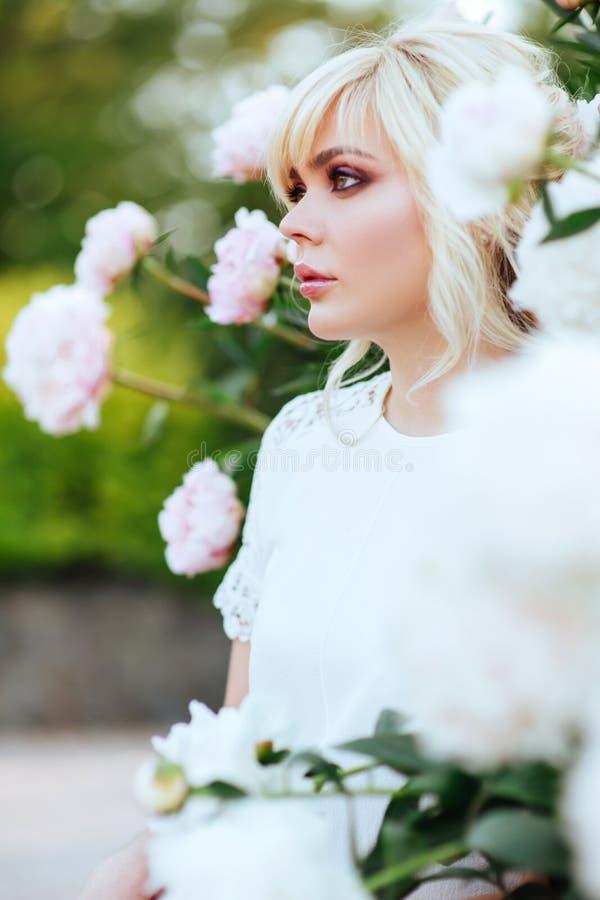 Fin ext?rieure vers le haut de portrait de belle jeune femme dans le jardin de floraison Concept femelle de mode de ressort photos stock