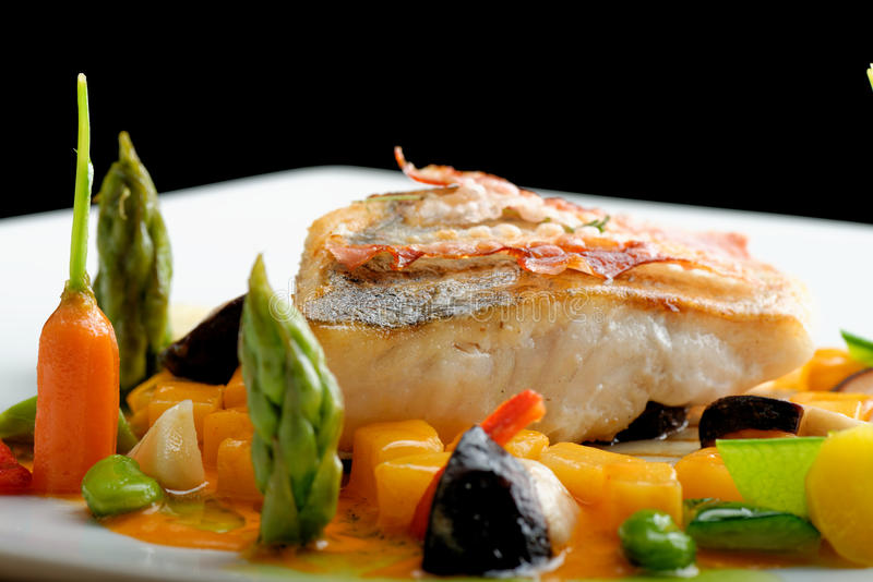 Fin filé för äta middag vit fisk som paneras i örter, och krydda med grillad bacon arkivfoton
