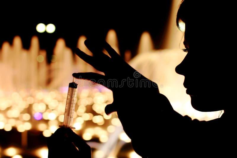 Fin flicka på gatan med injektionssprutan i hand arkivbilder