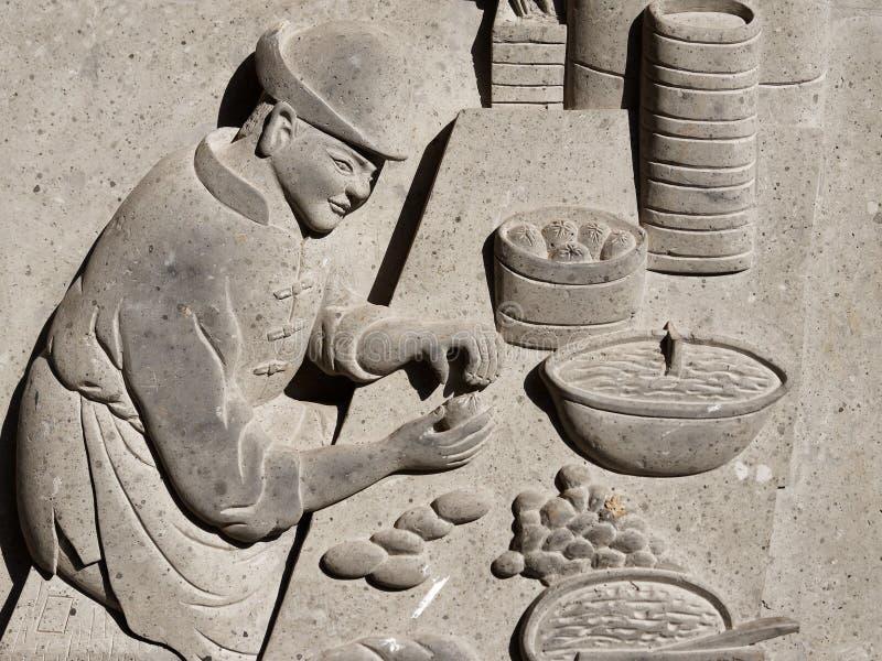 Fin forntida lättnad på en traditionell kinesisk spis för stenvägg som visar hur man gör ångade bullar arkivfoton