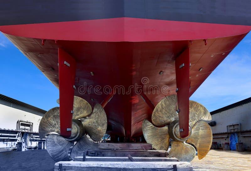 Fin jumelle de propulseur et cargo de réparation dans le dock sec de flottement photographie stock libre de droits