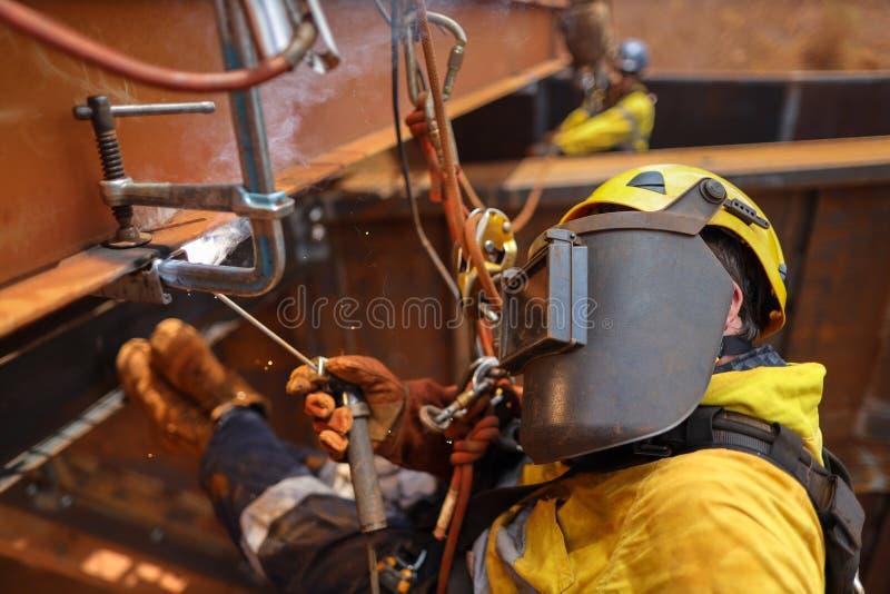 Fin latérale de tir de PPE de port de casque de harnais de corps de sécurité de chute de corde d'accès de soudeur d'abseiler indu photos libres de droits