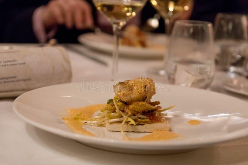 Fin matplatta med den grillade fisken på rostat bröd royaltyfria foton