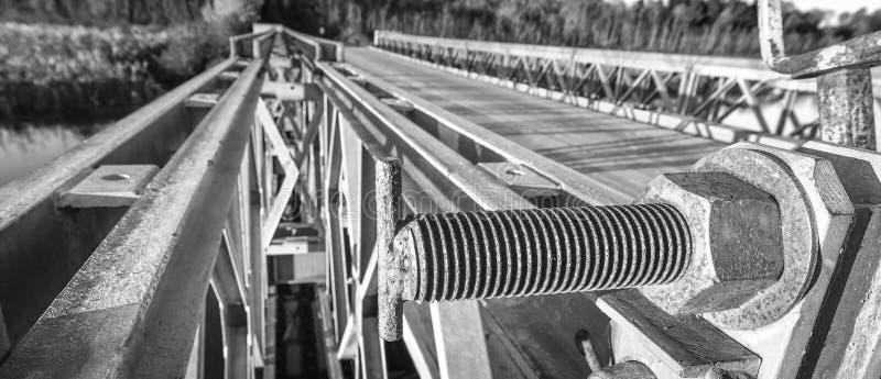 Fin noire et blanche de boulon avec l'écrou borgne, attachant la partie supérieure d'une porte en acier à une butée de pont photo libre de droits