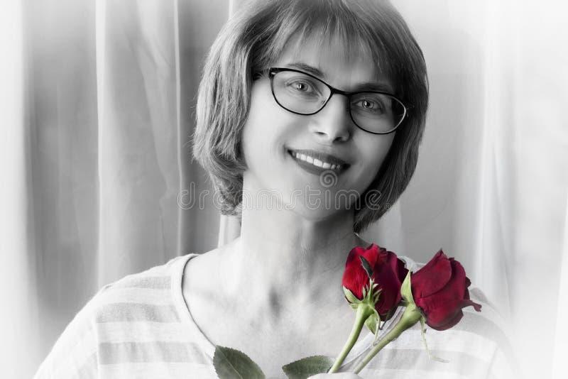 Fin noire et blanche vers le haut du portrait de la dame tenant la rose de rouge photographie stock