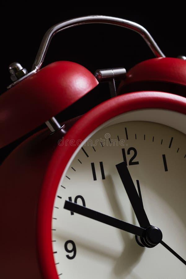 Fin rouge de réveil  It' ; s montrant dix minutes à douze o' ; c images stock
