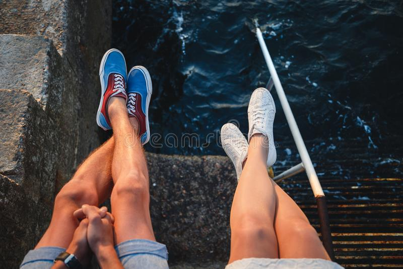 Fin supérieure vers le haut de la vue de jeunes jambes de couples dans des espadrilles presque se reposant sur la jetée à la mer, photos libres de droits