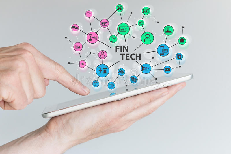 Fin Tech and mobile computing concept. Hand holding tablet with network of financial information technology objects stock image