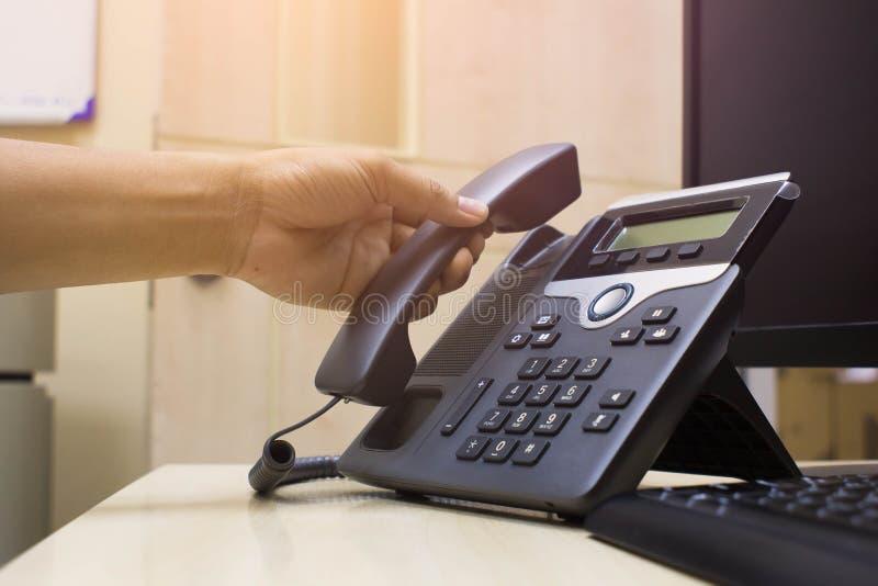 Fin tenant en main le téléphone au bureau, le téléphone de bureau et l'ordinateur et le clavier images stock