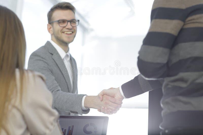 Fin vers le haut Associés de poignée de main dans un bureau moderne image stock