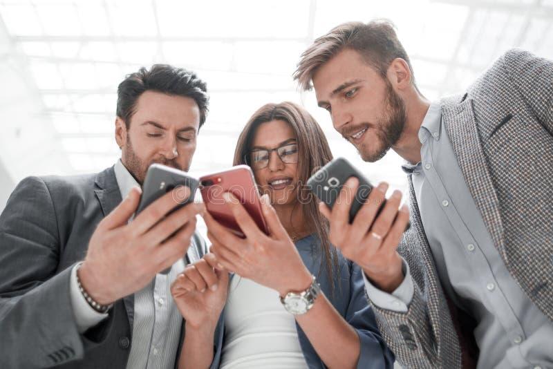 Fin vers le haut collègues d'affaires lisant SMS sur leurs smartphones photographie stock