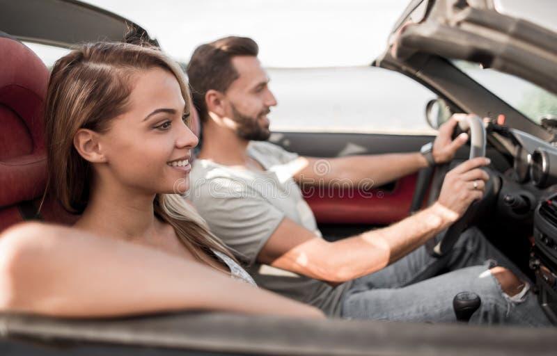 Fin vers le haut couples de sourire se reposant dans une voiture convertible photo stock
