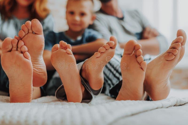Fin vers le haut de famille trois paires de pieds dans le lit photographie stock libre de droits