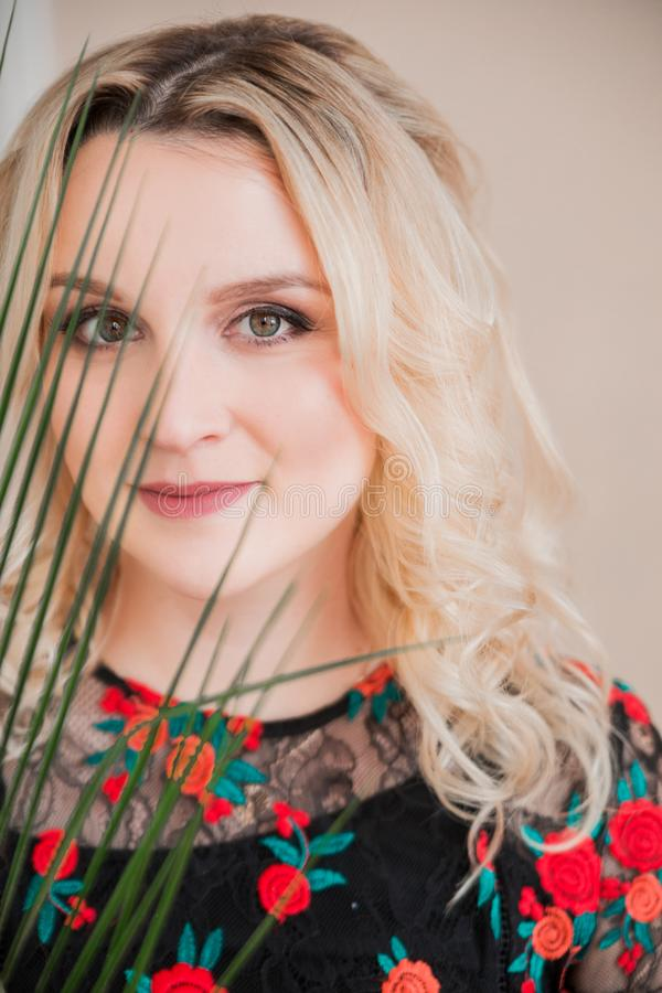 Fin vers le haut de femme blonde de visage de portrait avec la branche de paume photos stock