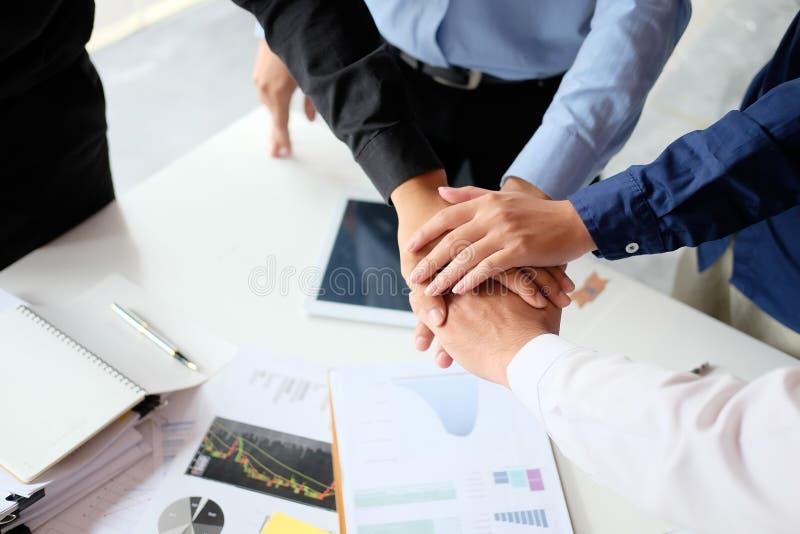 Fin vers le haut de jeunes hommes d'affaires remontant leurs mains sta images stock