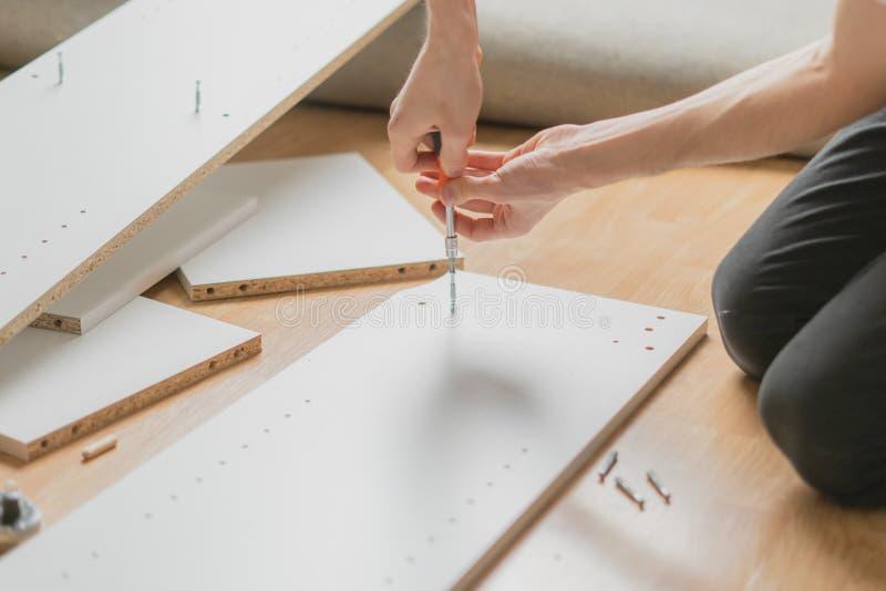 Fin vers le haut de l'homme assemblant de nouveaux meubles avec un tournevis b photographie stock