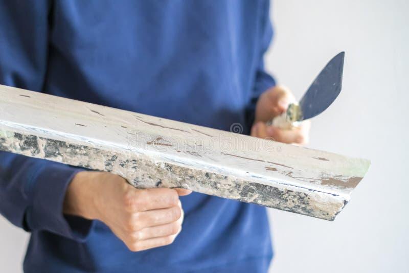 Fin vers le haut de l'homme tenant des couteaux de mastic plâtrant la maison f de mur, de fonctionnement et de réparation photos libres de droits